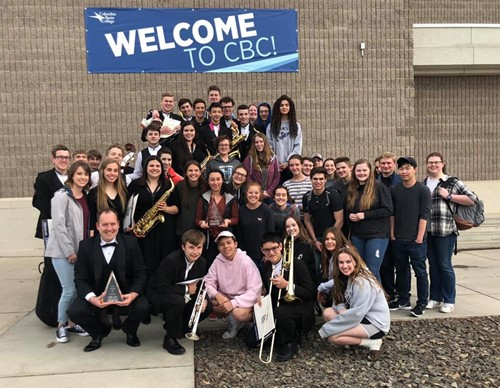 HHS band members and director Corey McEnry hold trophies at Columbia Basin College